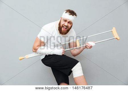 Cheerful playful young man having fun with crutch over white background