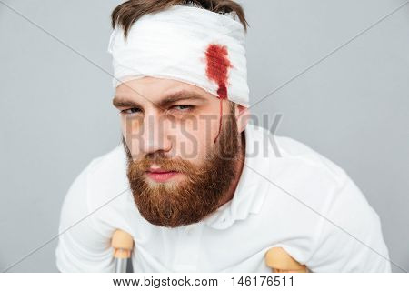 Sad desperate miserable injured man with crutches and head bandage over gray background