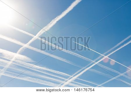 Airplanes in blue sky with Vapor Trail. Condensation trails of planes in the sky. Vertical and horizontal lines in the sky like chessboard or cellular field. Peace. Aviation. Travel concept.