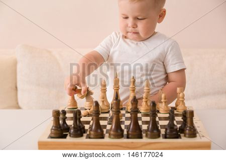 Cute toddler boy playing chess in the room. Little clever child playing chess at home. Education concept. Preschooler with chess.