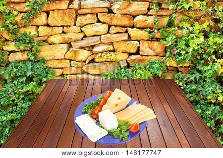 savory set of cheese greek goat feta yellow fromage french on blue plate over wooden tablen at outdoor garden near old ancient wall