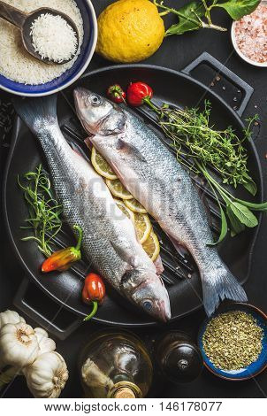 Ingredients for cookig healthy fish dinner. Raw uncooked seabass fish with rice, lemon, herbs and spices on black grilling iron pan over dark background, top view,