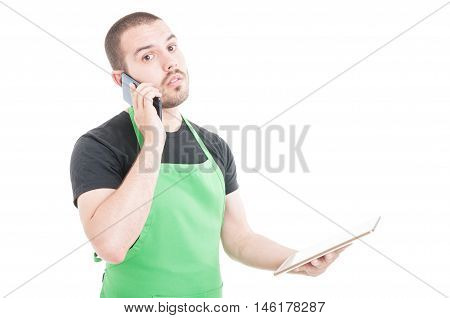 Serious Hypermarket Clerk Talking At Phone And Holding Tablet