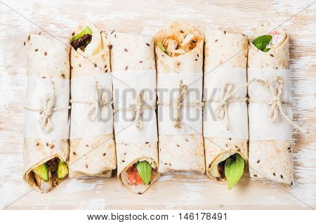 Tortilla wraps with various fillings on shabby white painted wooden background, top view, horizontal composition. Healthy snack or take-away lunch bites