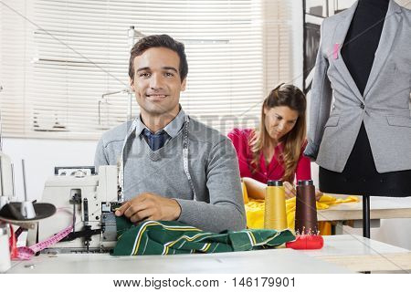Smiling Tailor Sitting At Workbench In Sewing Factory
