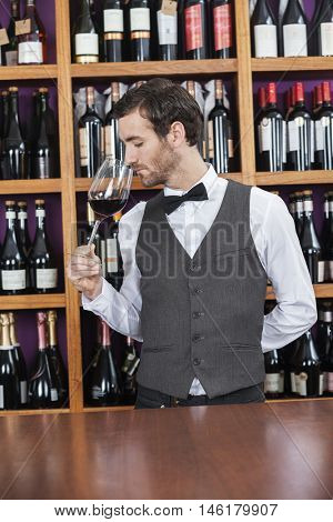 Bartender Smelling Red Wine At Counter