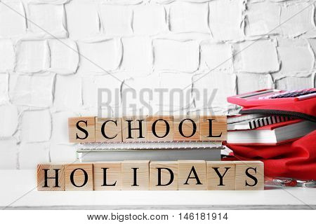 Words SCHOOL HOLIDAYS with stationery set on light background