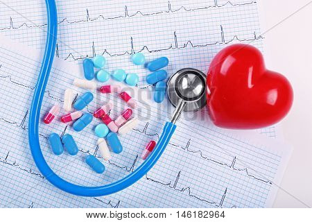 Stethoscope, pills and heart on table