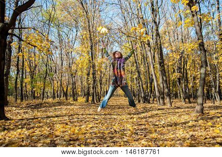 Joyful woman jumping for joy tossing up leaves