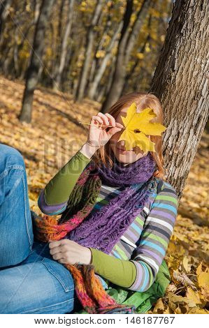 Red-haired woman smiling through the autumn leaf