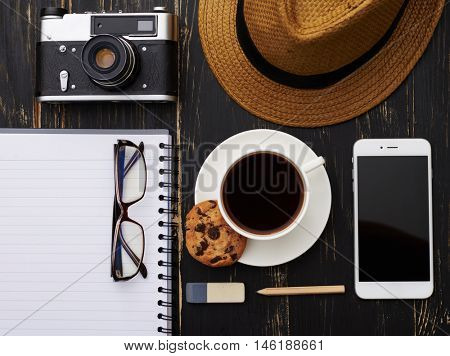 Top view of stylish man working surface mockup - notepad with stationery, hat, vintage camera, phone, eyeglasses and a cup of coffee with cookie