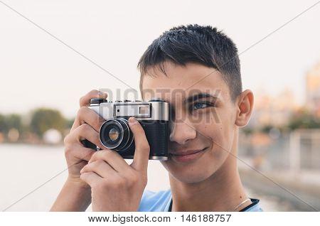 Cute boy teenager with vintage rangefinder camera. Close-up Photo.