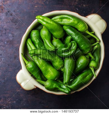 Food and drink, still life, moody concept. Raw green peppers pimientos de padron traditional spanish tapas on a black rusty table. Selective focus top view flat lay