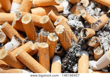 Big pile of put out cigarettes in an ashtray. Smoking smoker addiction health hazard lung cancer concept.