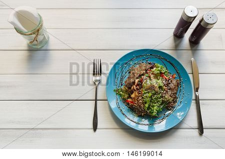 Restaurant food on white wood, top view with copy space. Warm meat salad with sesame, vegetables and lettuce on blue plate. Appetizing dish served with soy sauce, dinner meal.