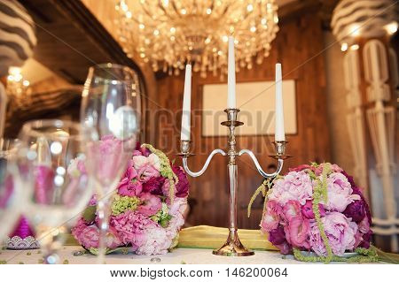 gorgeous flower arrangement at the wedding table. And candleholder for three candles on the background of elegant chandeliers