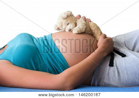 Pregnant lying woman in teal shirt with beautiful belly isolated on white background. Woman holding the Teddy bear on the belly