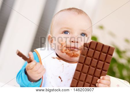 Baby boy eating chocolate.His face and hands smeared with chocolate.