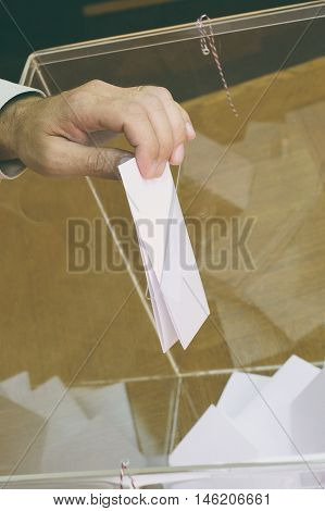 Image of a ballot box and hand putting a blank ballot insideelections voting concept.