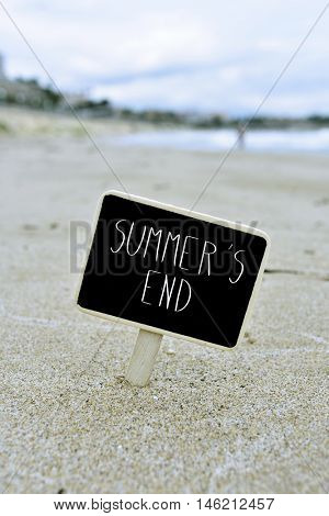 closeup of a black signboard with the text summers end written in it, on the sand of a beach