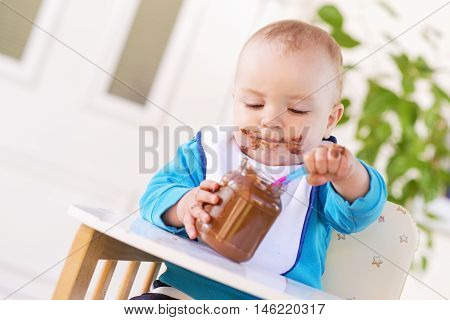 A baby grabbing a jar of chocolate cream while sitting in his high chair.His face and hands smeared with chocolate cream.