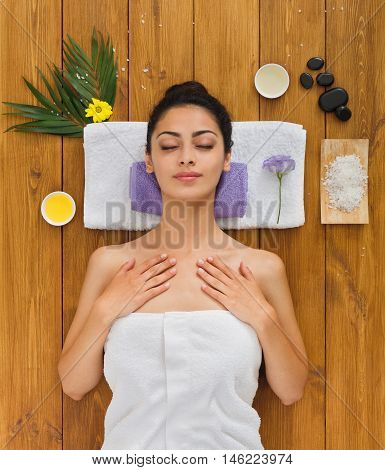 Portrait of woman patient in ayurveda spa wellness center lying relaxed on wood with aroma spa accessories. Young beautiful indian girl with ideal clean skin resting with closed eyes in beauty parlor.