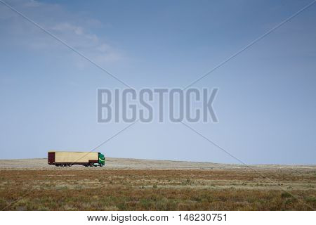 Side view of delivery-truck driving along countryside road on blue sky.copyspace