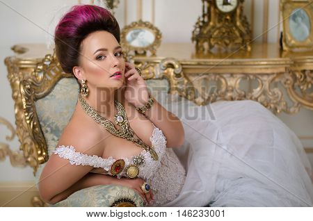 beautiful girl with curvaceous rococo hair lies in a lush white dress on a beautiful sofa in baroque interior.