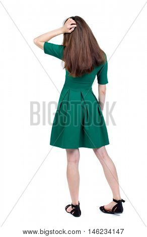 back view of standing young beautiful woman. slender brunette in a green short dress thoughtfully scratching his head.