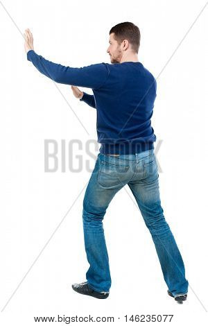 back view of business man pushes wall. bearded man in blue pullover shoves something on the side.