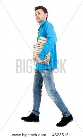 side view of going man carries a stack of books. walking young guy . curly-haired student in a blue warm jacket comes with books and looking at the camera.