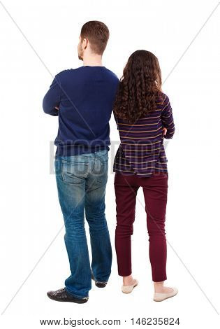 Back view of young embracing couple (man and woman) hug and look into the distance. Swarthy girl and a bearded man standing back to back.