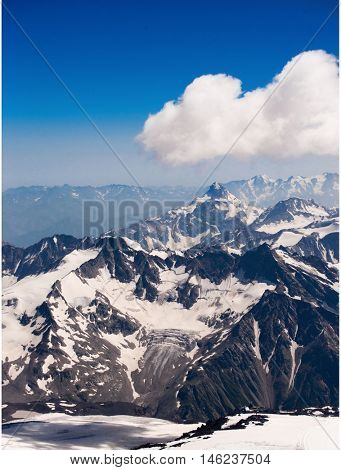 Mountain landscape. snow-capped peaks of the mountains. The sharp peaks of the mountains in the snow, on a background of clouds. background for ski resort