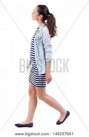 back view of walking curly woman. Swarthy girl in a checkered dress goes to the side and looking up.