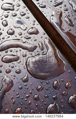 Drops of water on a wooden bench. After rain.