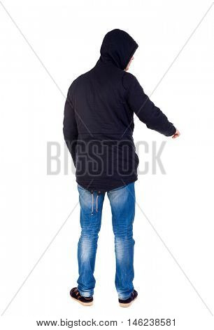 Back view of pointing young men in parka. Young guy gesture. Rear view people collection. The guy while wearing a hood on his head is pointing down.