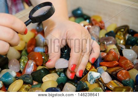 Colorful smooth stones looking through a magnifying glass. Study of rocks and minerals. Round semi-precious minerals. Polished minerals. Beautiful natural stones. Geology scattering of stones.
