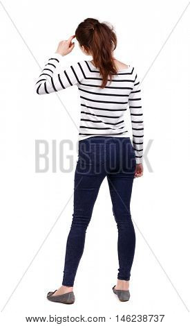 back view of standing young beautiful woman. girl watching. Girl in a striped sweater thoughtfully scratching his head.