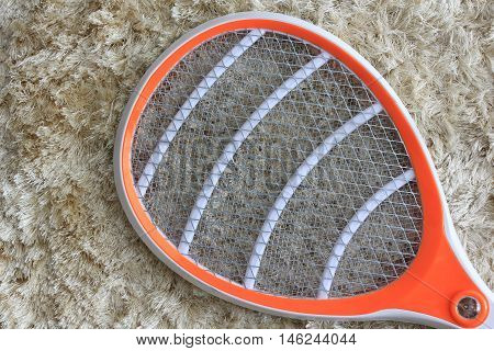 Electric fly swatter on brown shaggy carpet