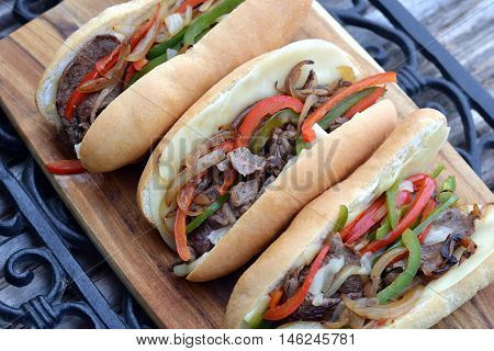 Three Philly Cheese Steak Sandwiches: Ingredients include hoagie style buns with provolone cheese slices, rib eye steak slices, grilled bell peppers and onions.