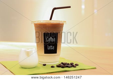 Iced coffee latte on wood table. In Plastic cup