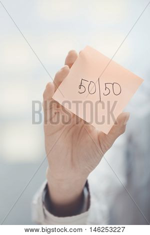 Hands holding sticky note with Fifty-fifty text