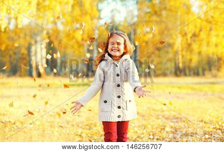 Happy Little Girl Child Having Fun Playing With Yellow Leafs In Sunny Autumn Day