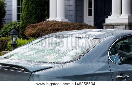 Snow and ice on back of car window. Cold weather concept for driving cars during winter. Selective focus on rear window of car with partial home in background.