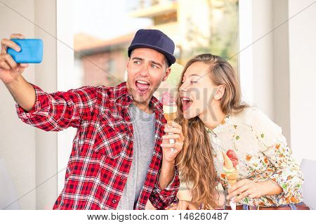 Playful couple eating ice cream taking funny selfie outside shop - Girlfriend teasing boyfriend with funny face in self photo on joyful holiday moment - Concept of friends having fun using technology