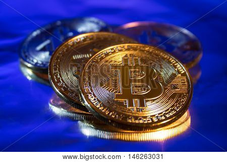 Photo Golden Bitcoins new virtual money Close-up on a blue background.