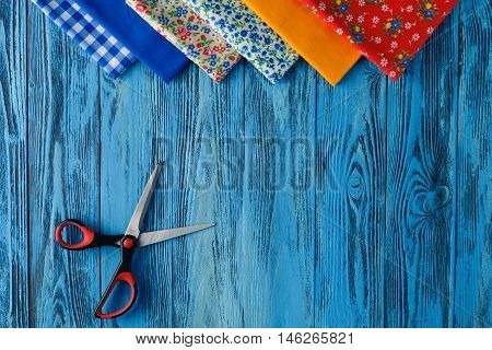 Sewing items on blue wooden table, top view