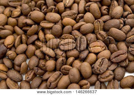 Roasted Coffee Beans background texture. Arabic roasting coffee - ingredient of hot beverage. Brown coffee beans for background and texture.