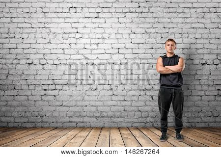 Front view of muscled young man standing with his arms folded on the background of white brick wall. Wellbeing. Muscleman. Workout and fitness.
