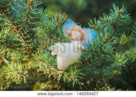 White Angel with blue wings, handmade, on a green spruce Christmas decorations